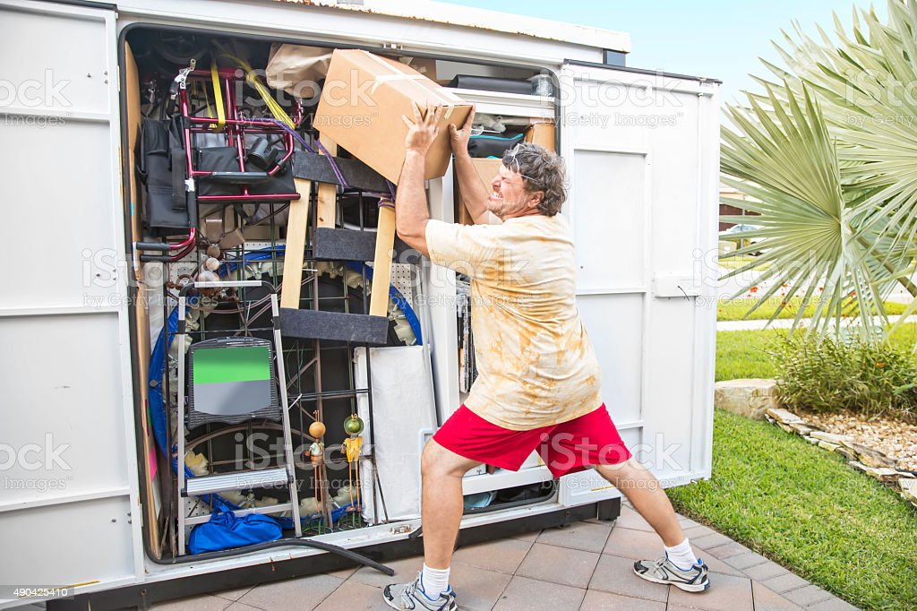 Moving Series: Frustrated man pushing carton in moving container stock photo