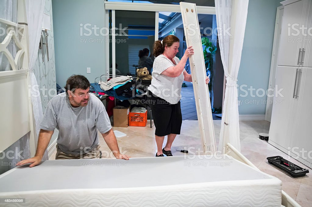 Moving series: Man and woman disassemble bed on moving day stock photo