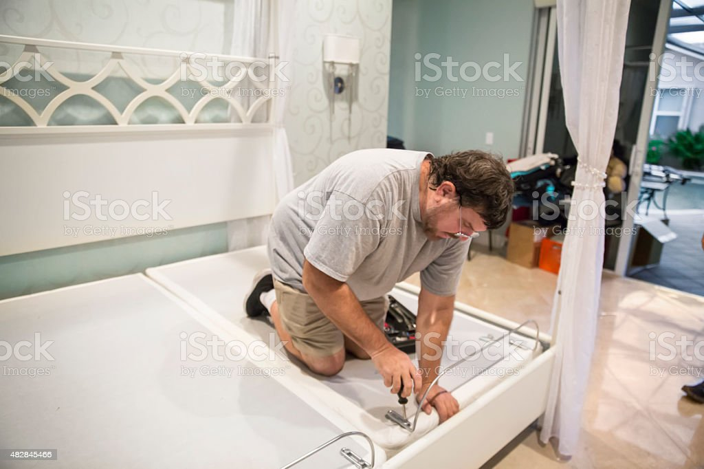 Moving series: Man disassembles adjustable bed to move it stock photo