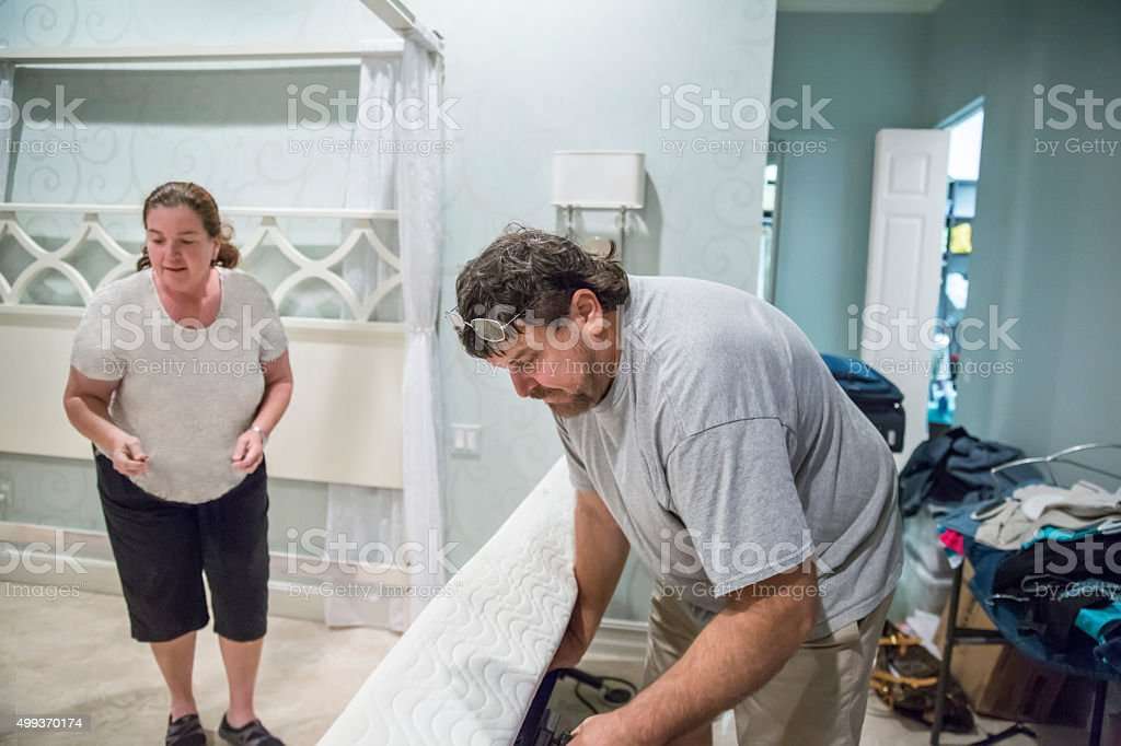 Moving series: Man disassembles bed on moving day stock photo