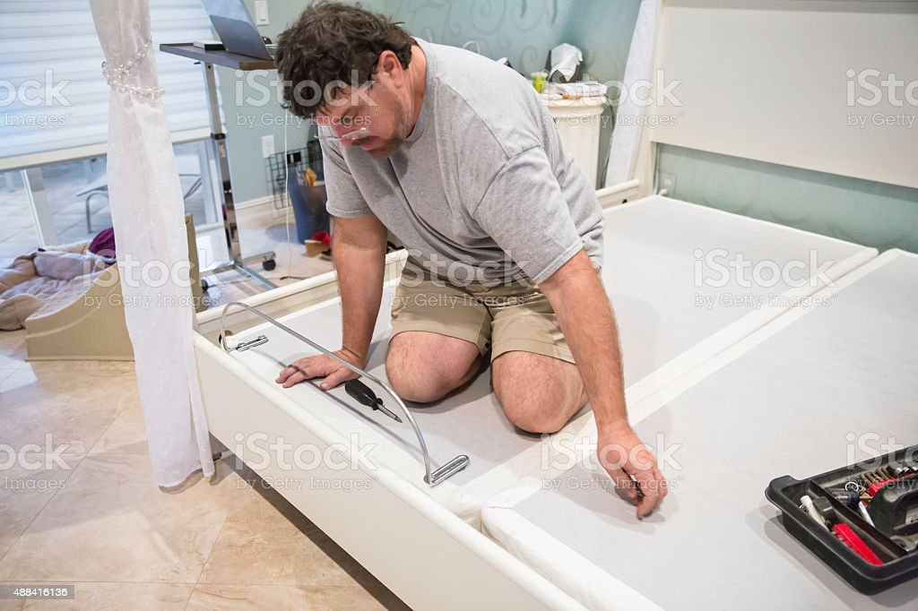 Moving series: Man takes apart adjustable bed to move it stock photo