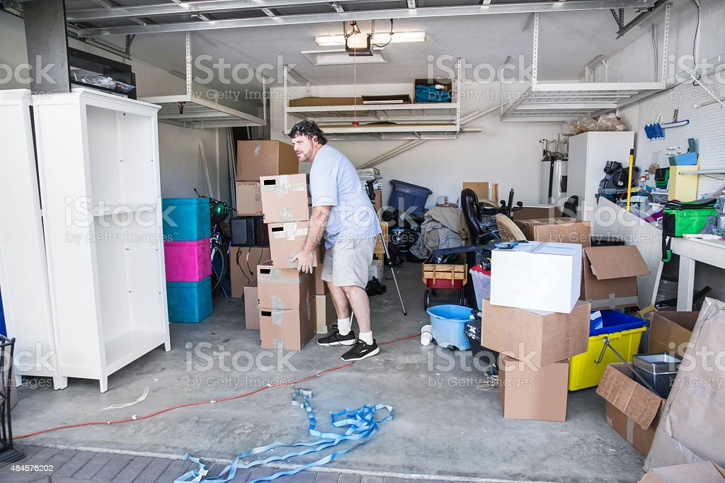 Moving Series: Mover in garage lifting boxes to move stock photo