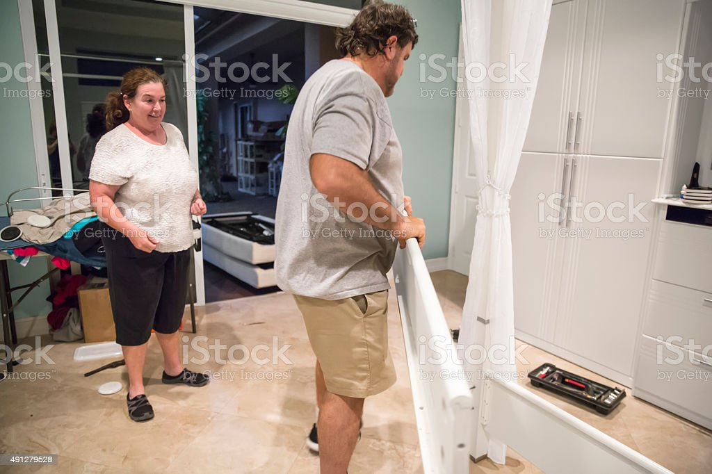 Moving series: Worker and homewoner take apart bedroom stock photo