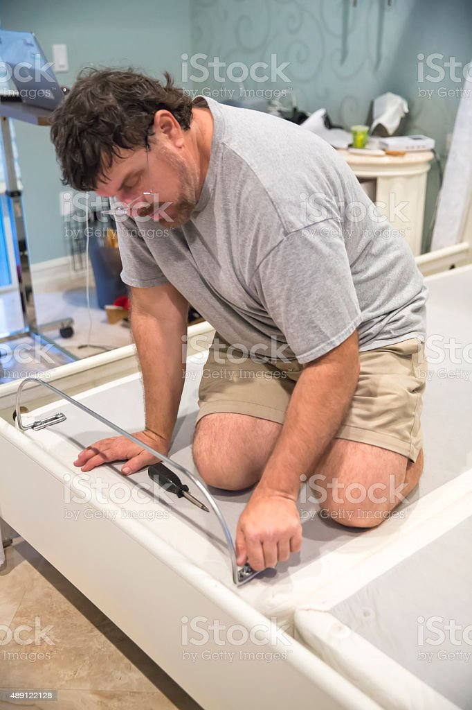 Moving series: Worker disassembles adjustable bed on moving day stock photo