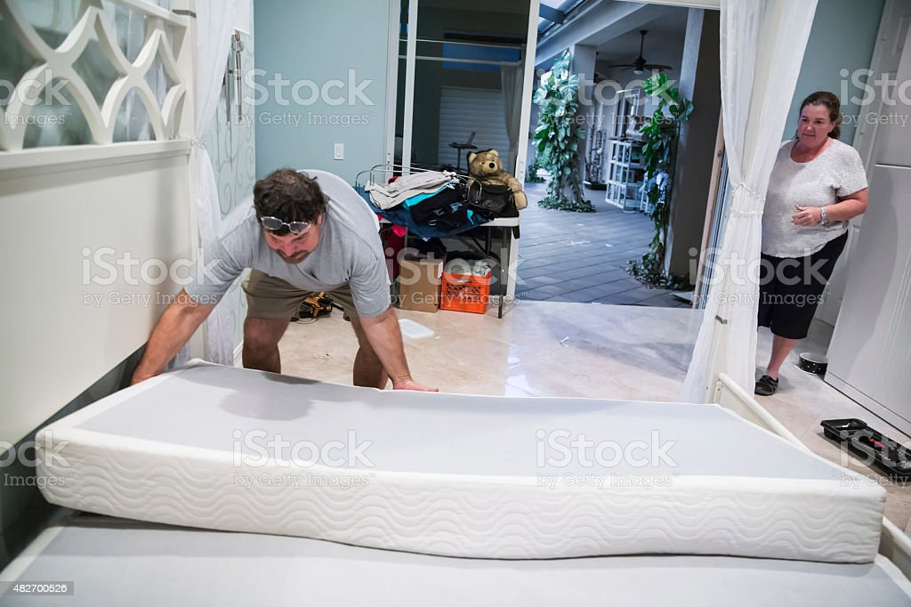 Moving series: Worker disassembles bed on moving day stock photo