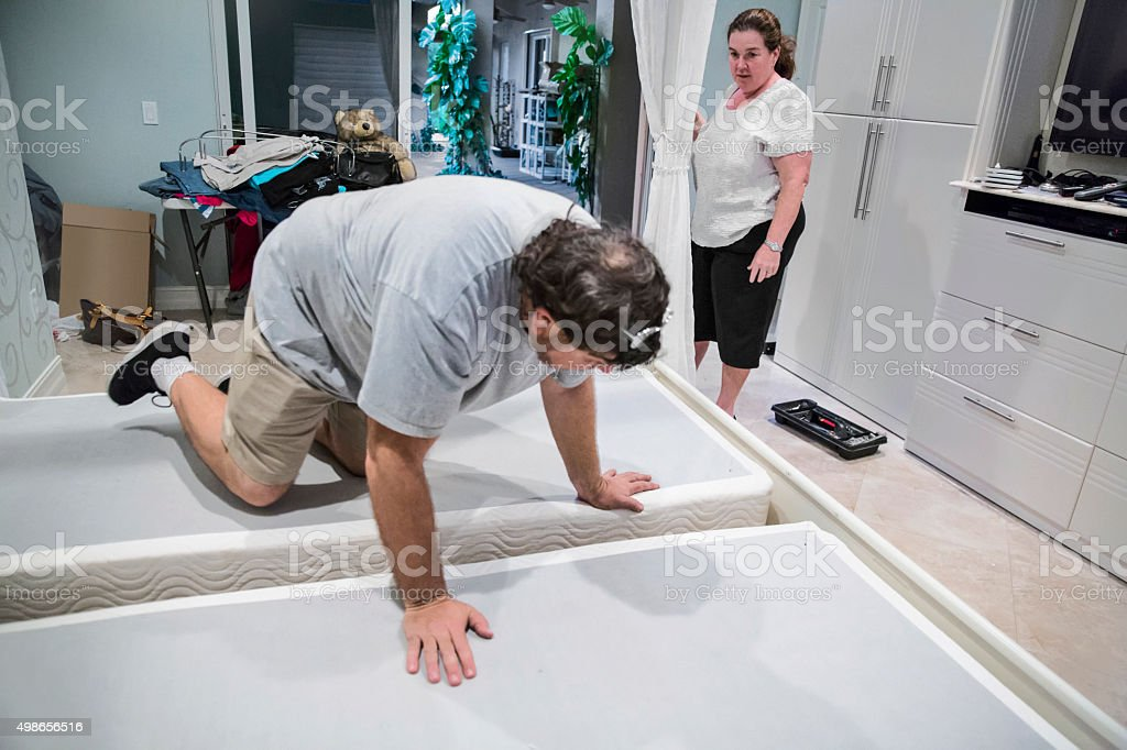 Moving series: Worker takes apart king bed on moving day stock photo