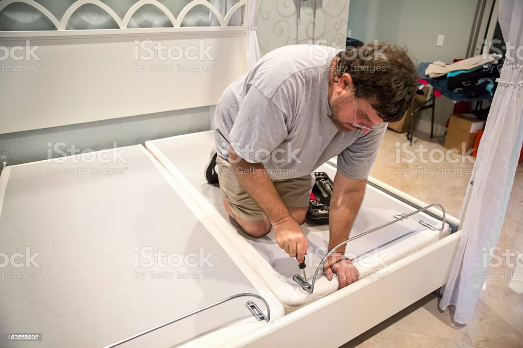 Moving series:Worker unscrewing bar on adjustable bed box spring stock photo