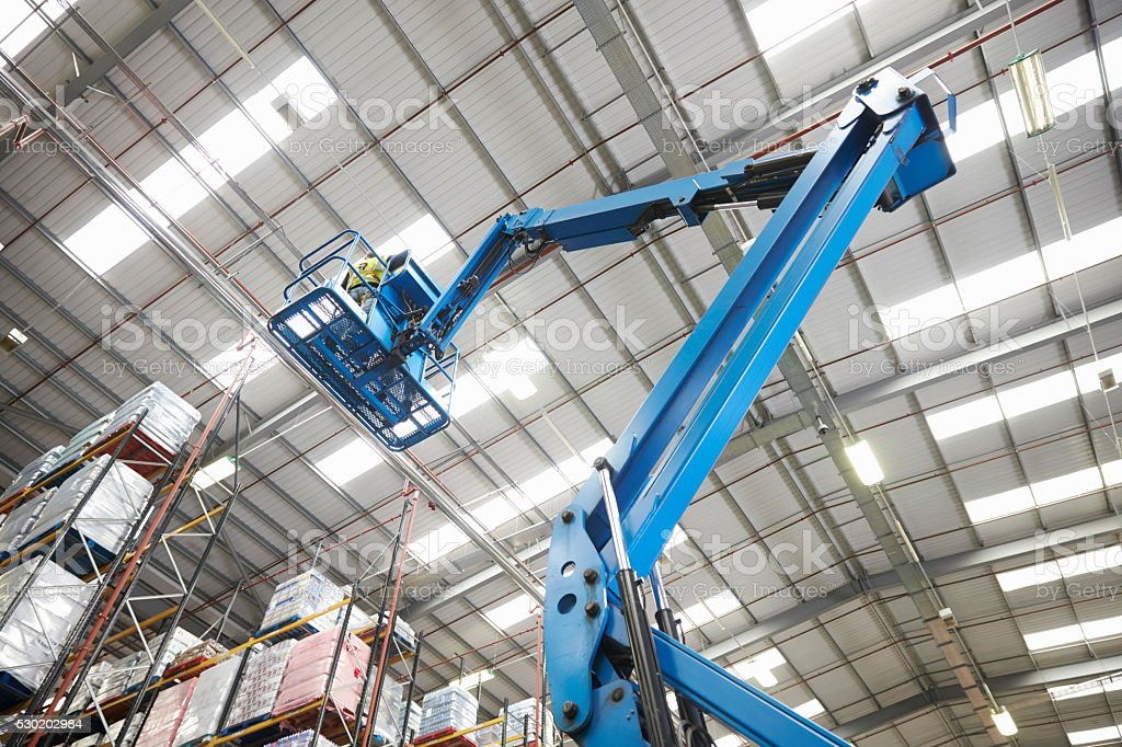 Moving stock in a warehouse with a cherry picker, low angle stock photo