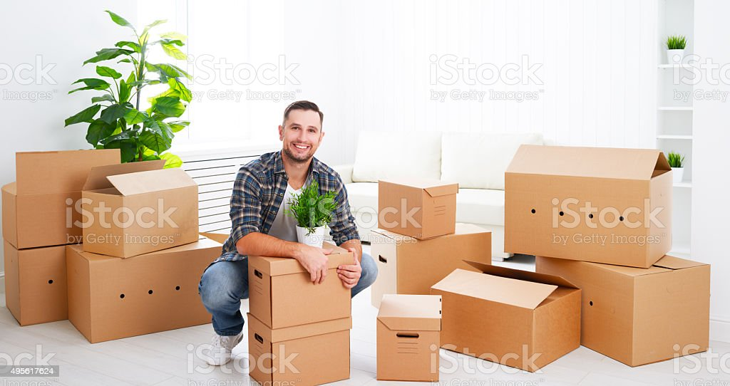 moving to a new apartment. happy man with cardboard boxes stock photo