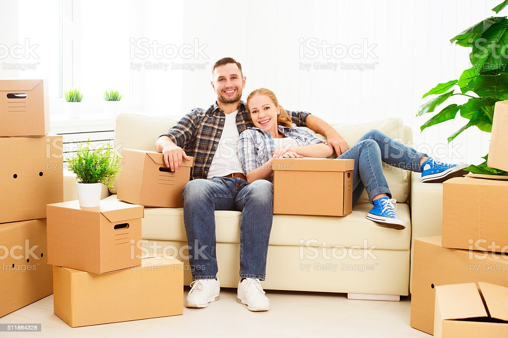 moving to new apartment. Happy family couple and cardboard box stock photo