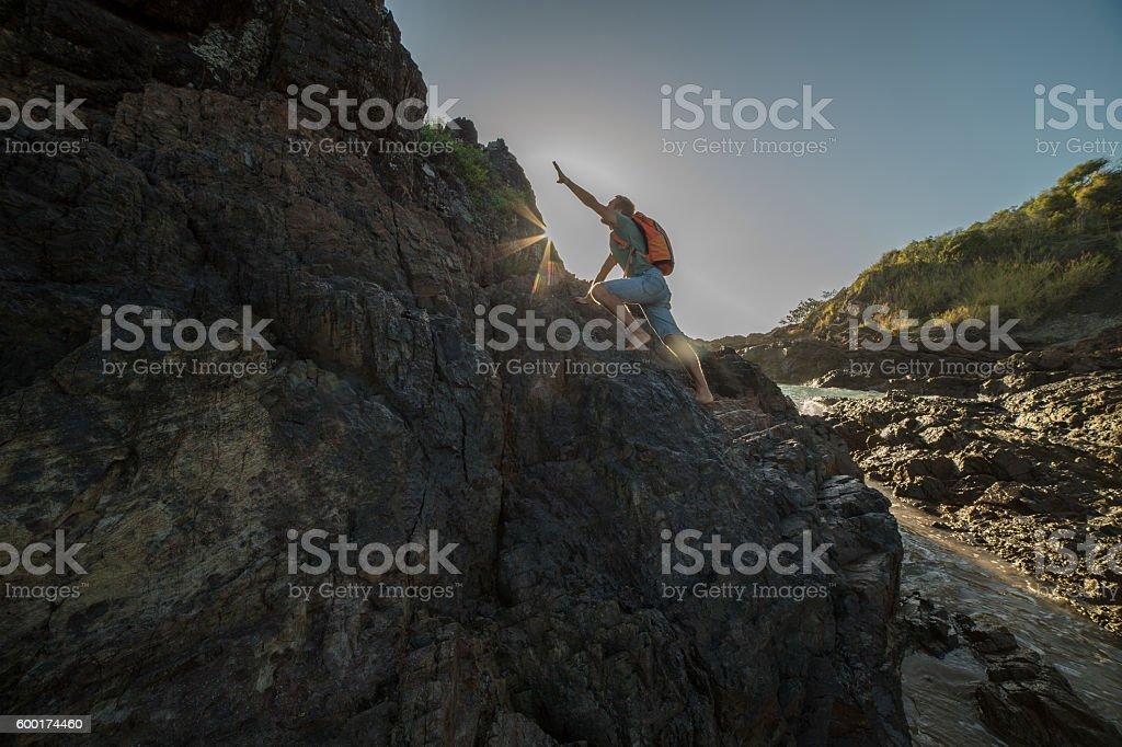 Young man climbs steep rock, towards sunlight. Low angle view.
