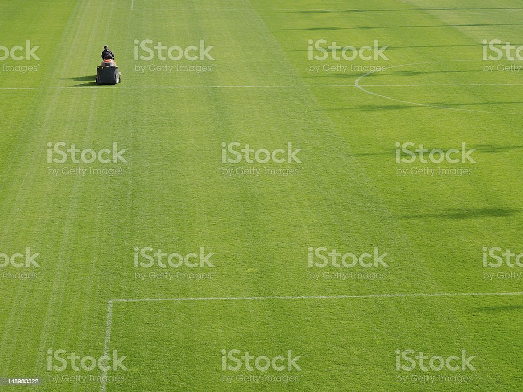 Mowing grass in a football stadium royalty-free stock photo