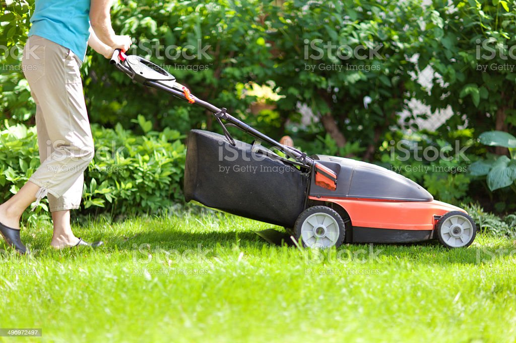 Mowing Grass Lawn with Electric Lawn Mover stock photo