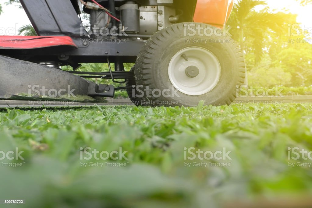 Mowing or cutting the long grass with a green lawn mower with burst light stock photo