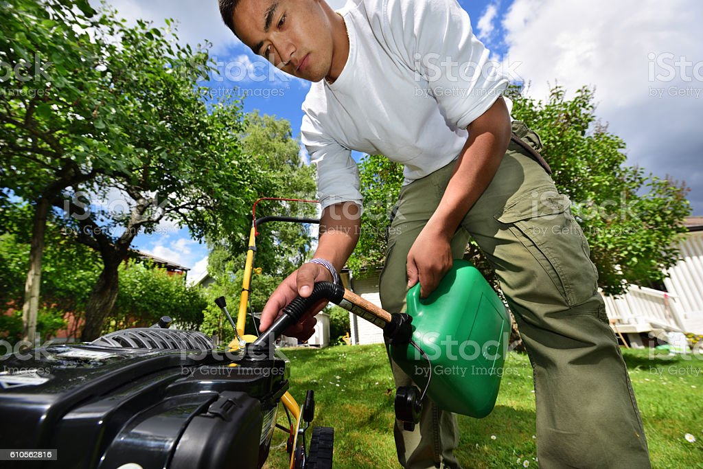 Mowing the lawn in nice green garden. Refuelling green petrol stock photo