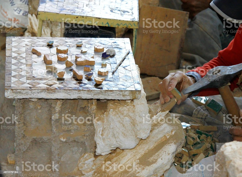 Mozaic artist shapes the pieces by breaking stock photo