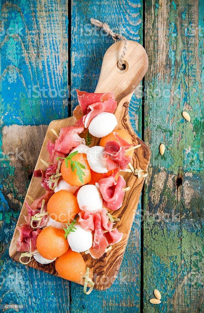 mozzarella and prosciutto with melon canapes on a cutting board stock photo