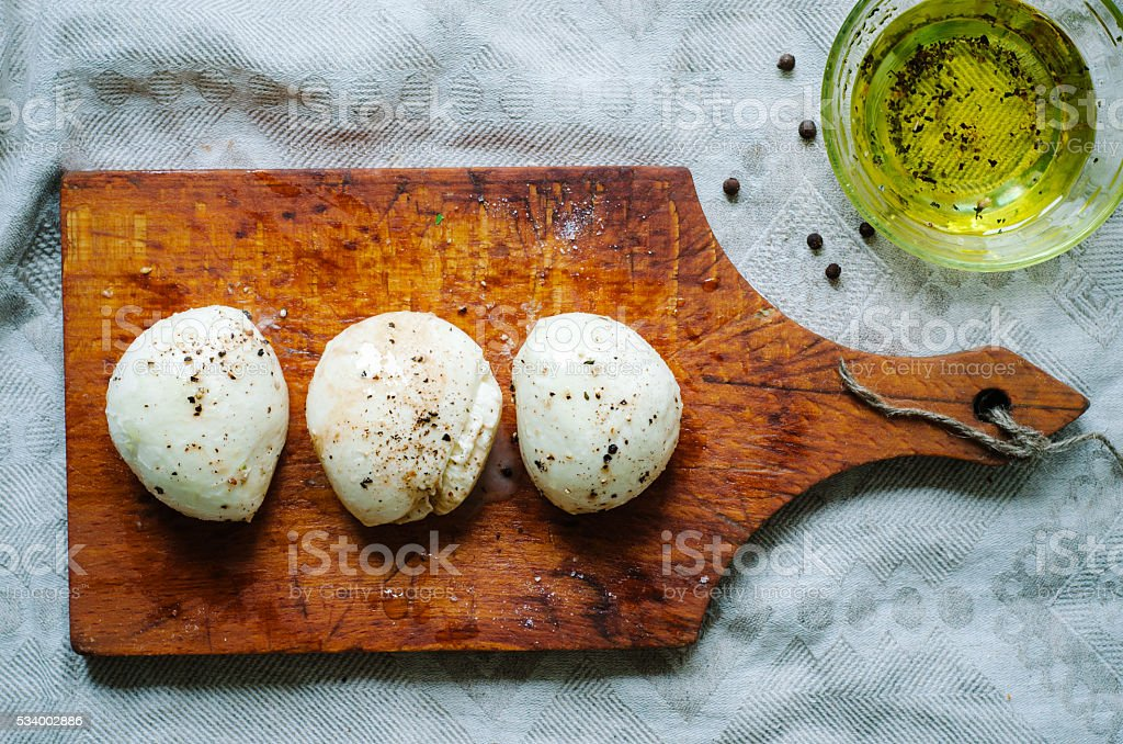 mozzarella balls on old wooden board with olive oil, stock photo