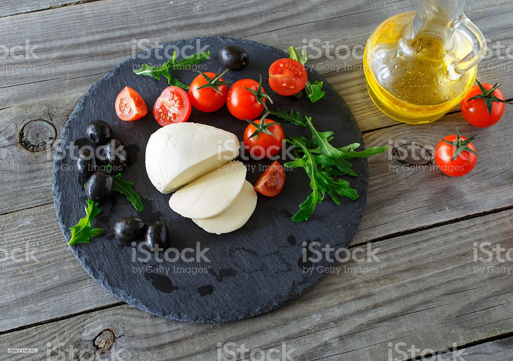 mozzarella cheese with cherry tomatoes, arugula and black olives stock photo
