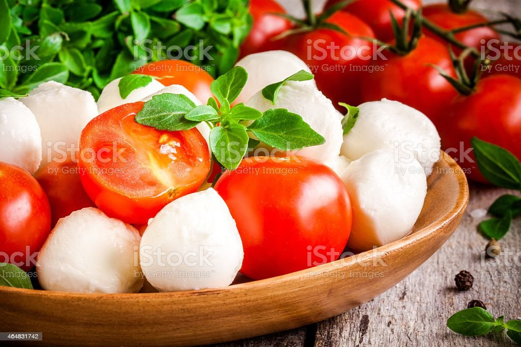 mozzarella, organic cherry tomatoes and fresh basil closeup stock photo