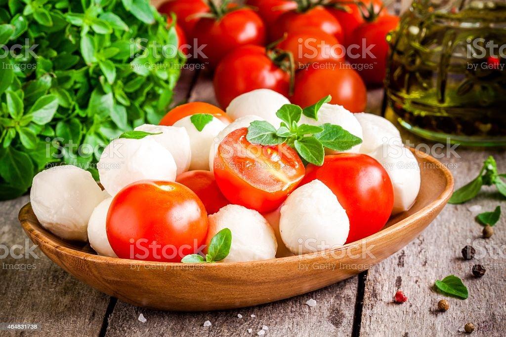 mozzarella, organic cherry tomatoes, fresh basil and olive oil stock photo