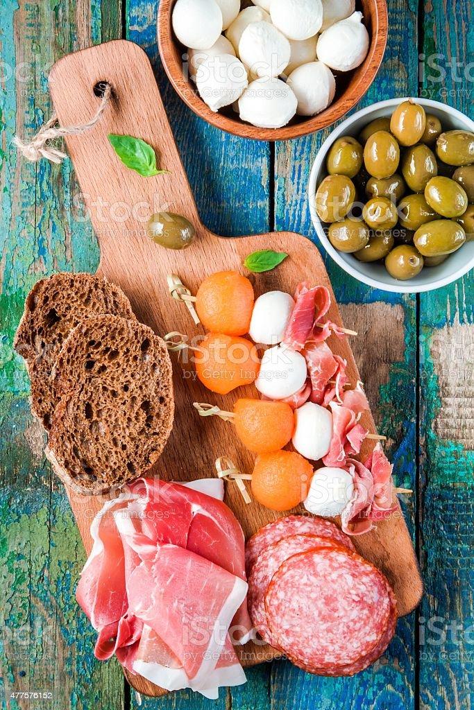 mozzarella, prosciutto, melon canapes with salami, olives and bread stock photo
