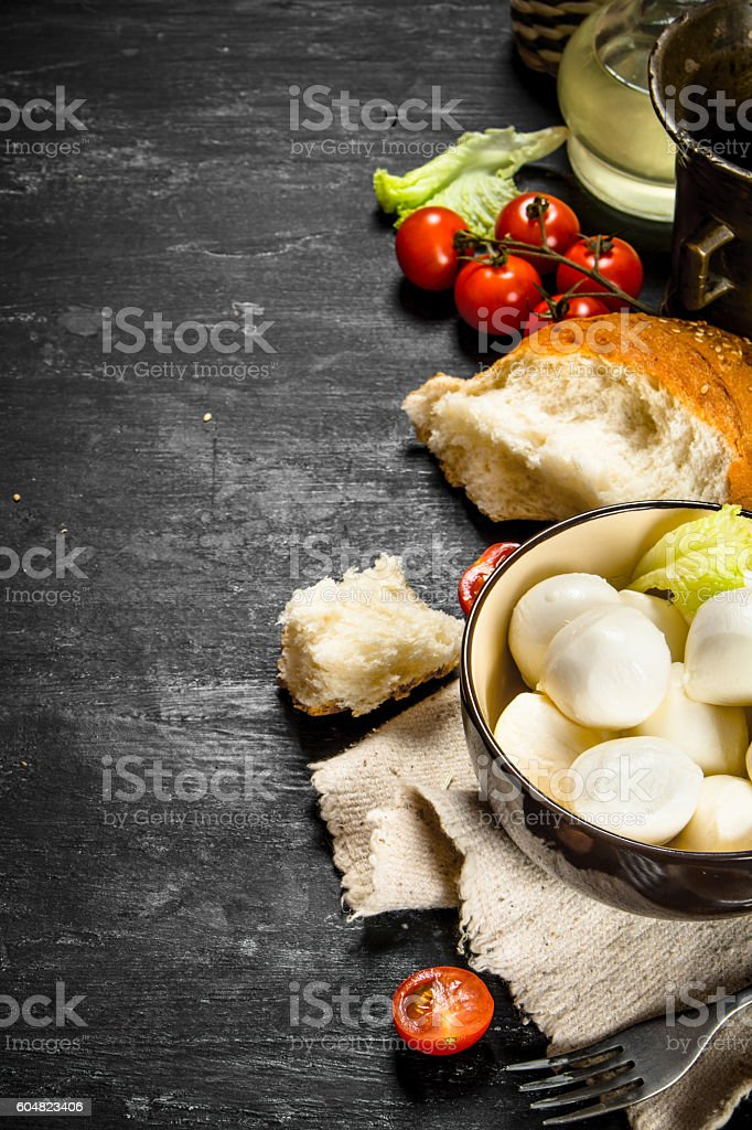 Mozzarella with fresh bread, tomatoes and greens. stock photo