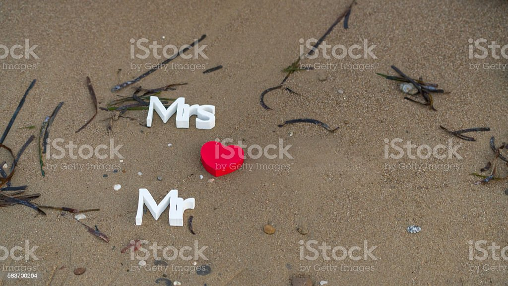 Mrs and Mr writing on sand stock photo