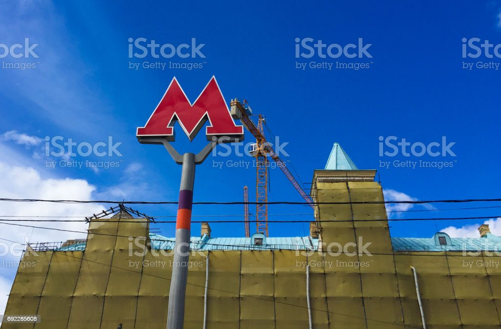 M-symbol of the metro against the sky and buildings stock photo