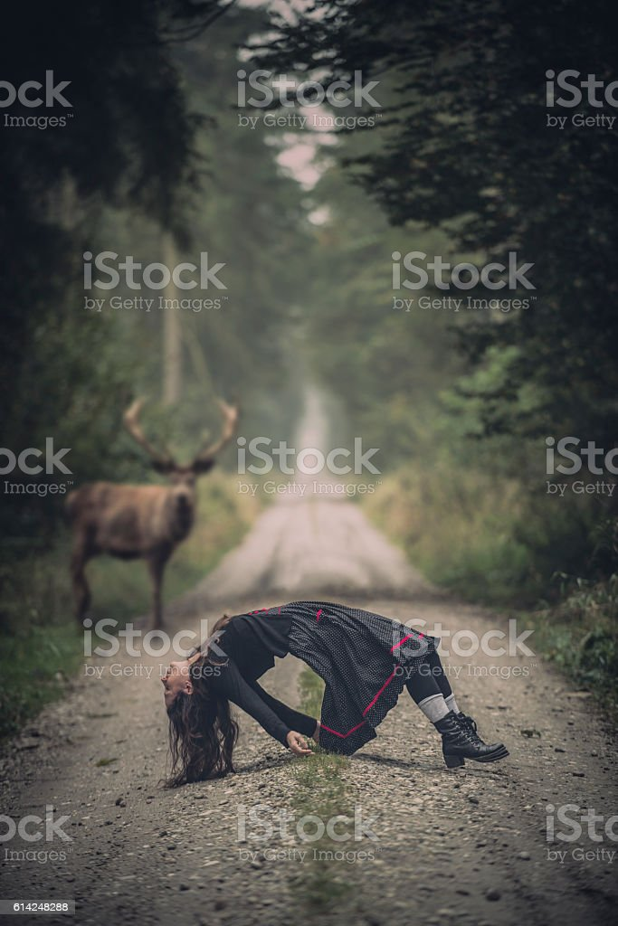 msystic scene with a women and a deer in forest stock photo