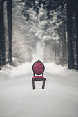 msystic scene with red chair in a winter forest