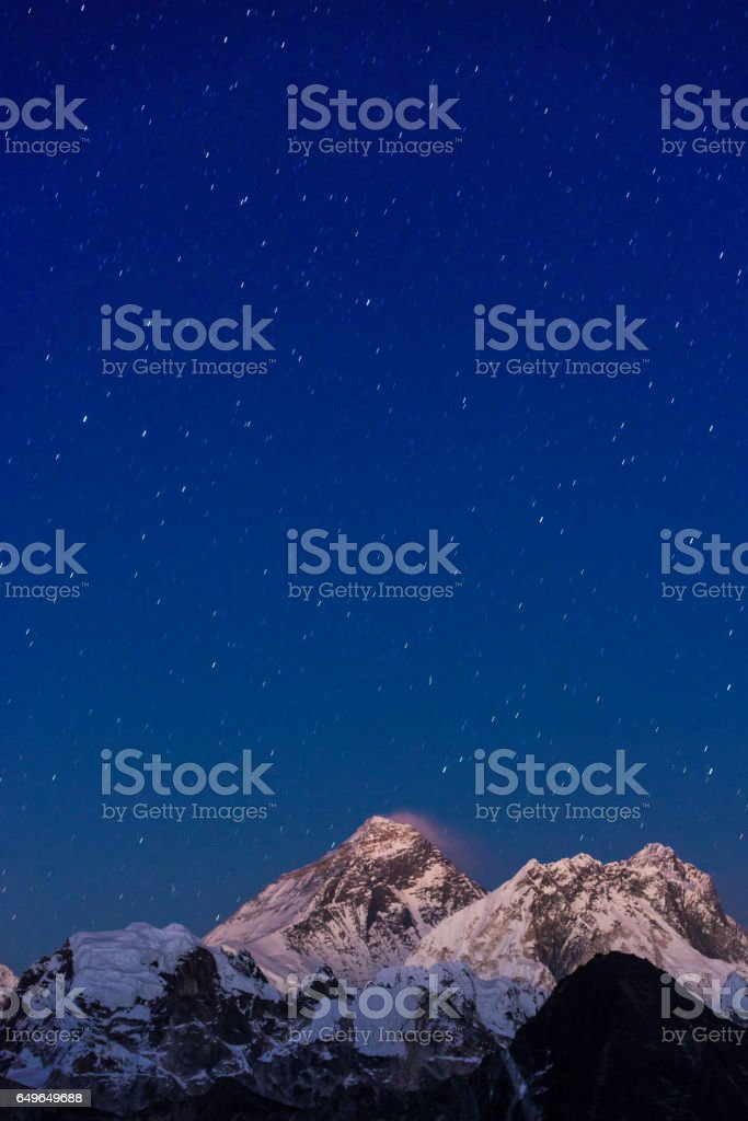 Mt Everest beneath starry night sky high in Himalayan mountains stock photo