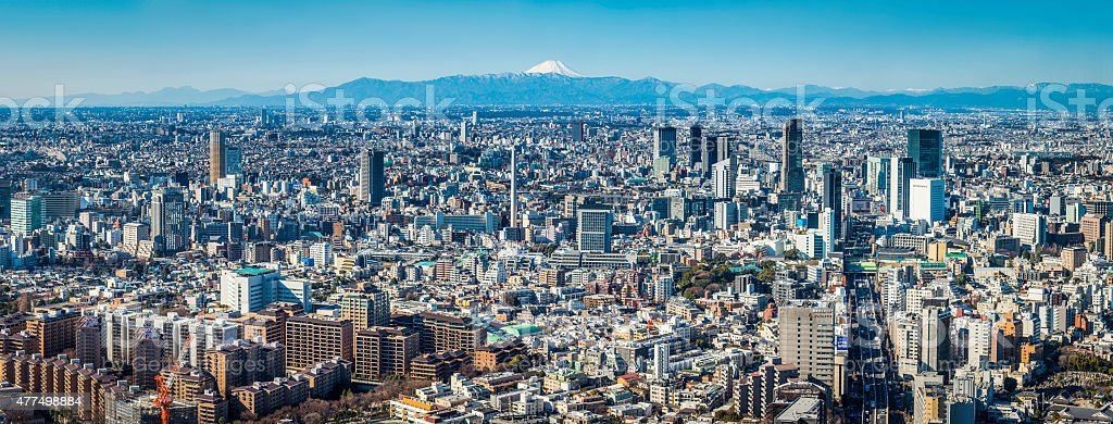 Mt Fuji iconic snowy summit overlooking crowded cityscape Tokyo Japan stock photo