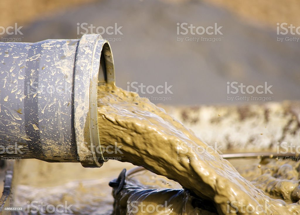 Mud flow from tube stock photo