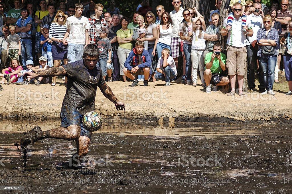 Mud football player kicking the ball stock photo