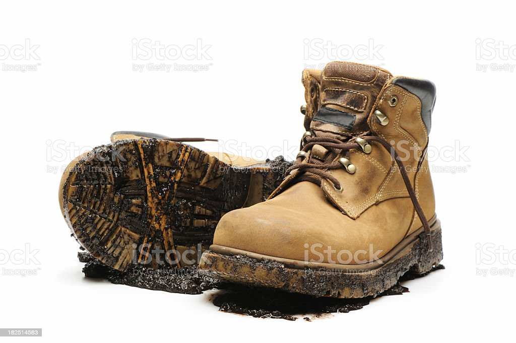 Muddy and dirty work boots on white background stock photo