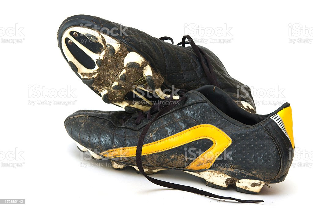 Muddy black and yellow football boots on a white background stock photo