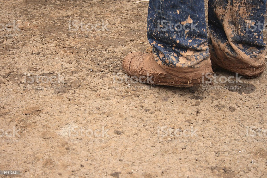 Muddy boots and mud splattered jeans stock photo