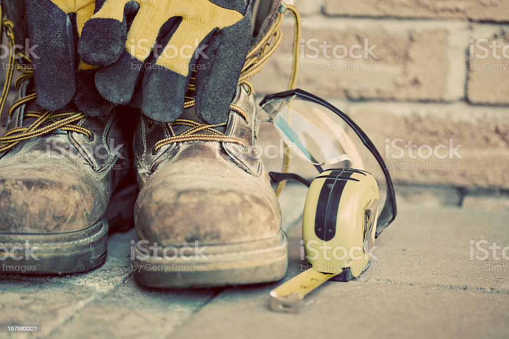Muddy construction work boots with gloves and tape measure stock photo
