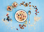 Muesli, berries with nuts seeds in bowl on blue background.
