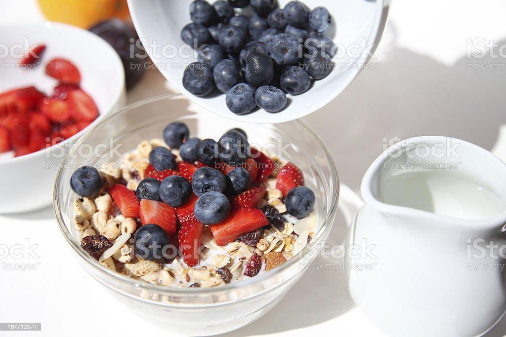 Muesli bowl on white table with fresh blueberries stock photo