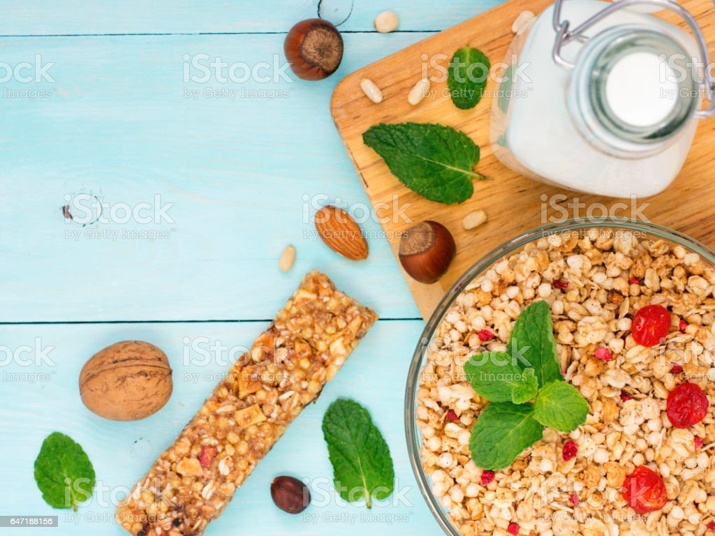 Muesli, milk and nuts on blue background stock photo