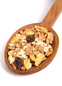 Muesli with dried fruits on wooden spoon