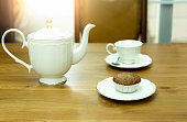 Muffin cake with cup of tea and teapot on table