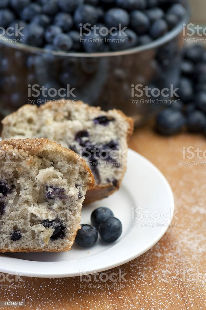 Muffin slices on white plate with bowl of fresh blueberries royalty-free stock photo
