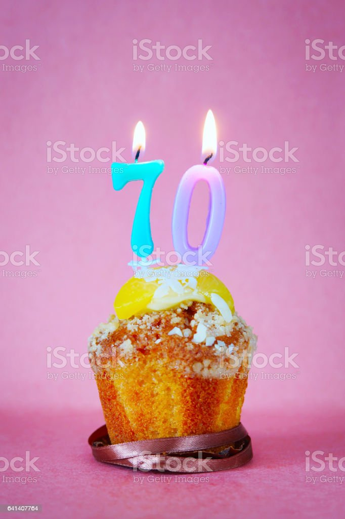 Muffin with burning birthday candles as number seventy stock photo