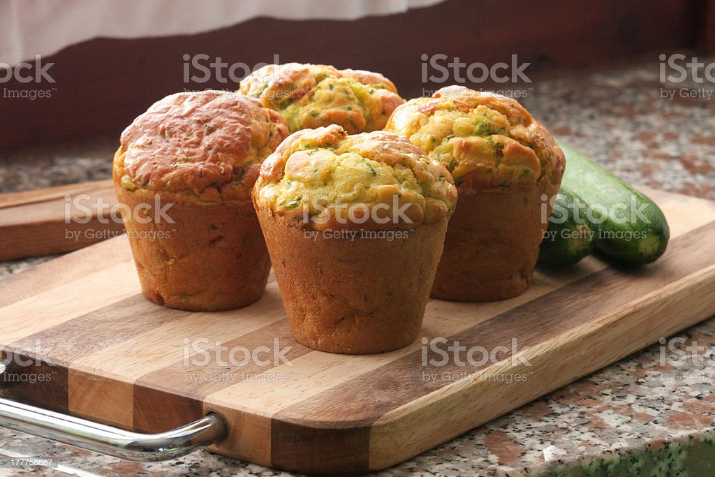 4 muffins made out of zucchini on a wooden board stock photo