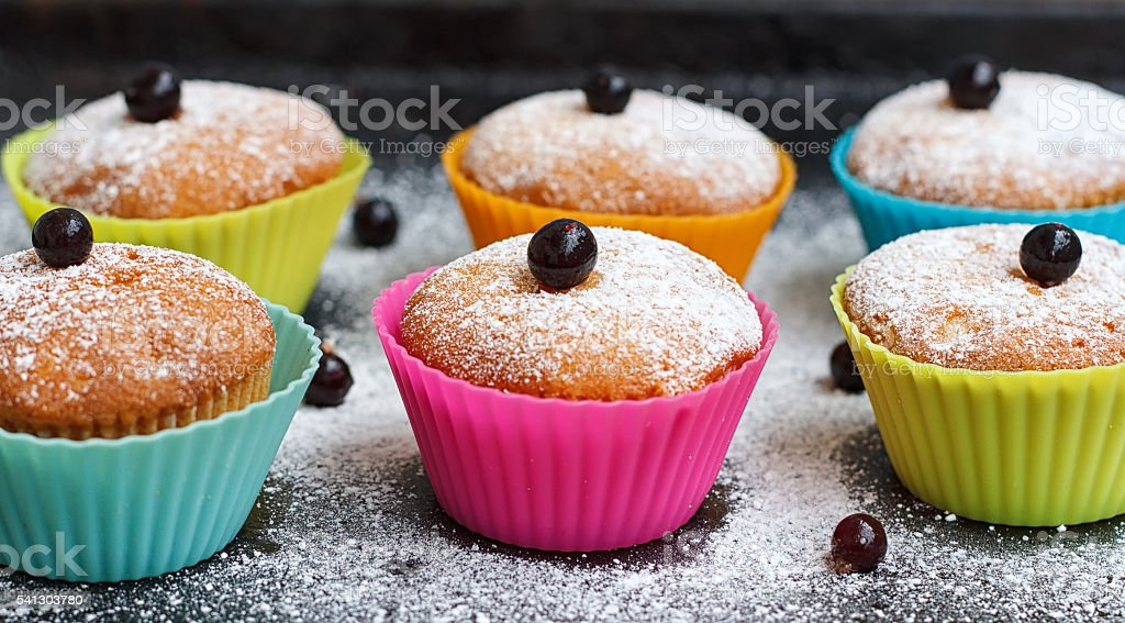 Muffins with black currant in silicone forms sprinkled stock photo