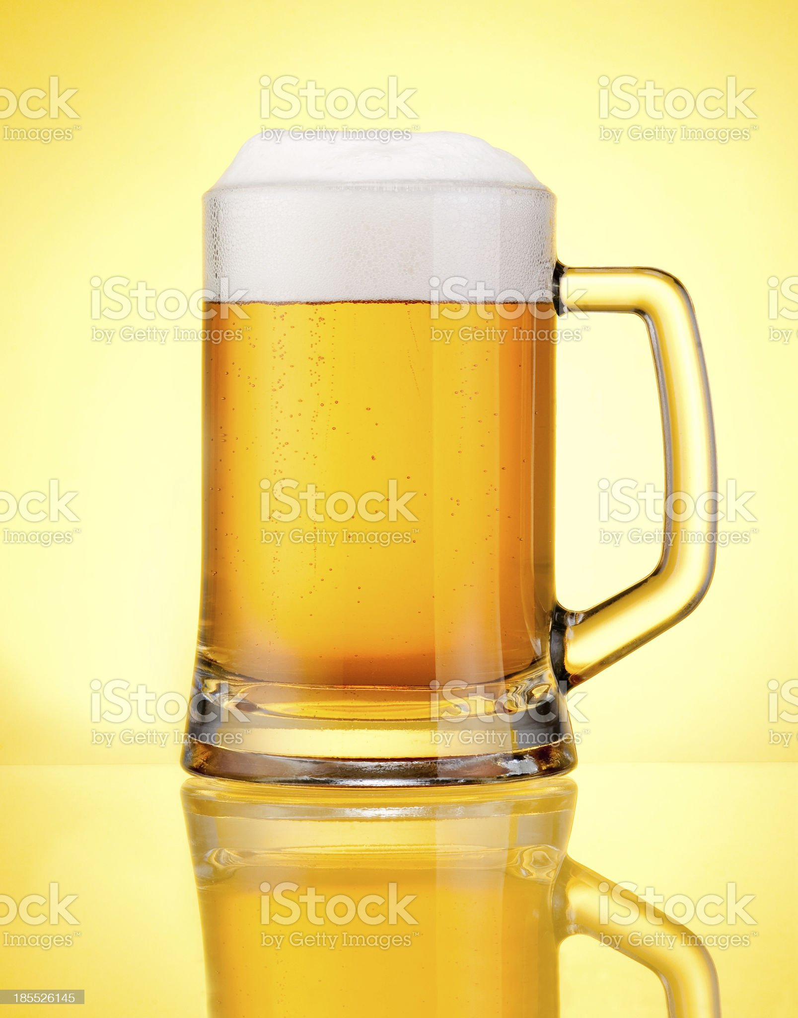 Mug fresh beer with cap of foam isolated over yellow royalty-free stock photo