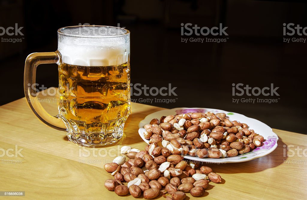 mug of beer and peanuts stock photo